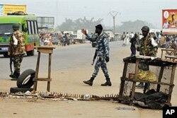 Des membres des forces loyales à Laurent Gbagbo à un point de contrôle à l'entrée du quartier pro-Ouattara d'Abobo, à Abidjan