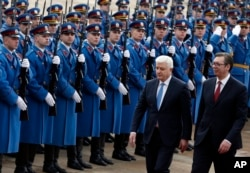FILE - Montenegro's Prime Minister Dusko Markovic, left, escorted by his Serbian counterpart Aleksandar Vucic, reviews the honor guard during a welcoming ceremony at the Serbia Palace in Belgrade, Serbia, Feb. 3, 2017.