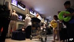 Passengers check into a flight at Abu Dhabi International Airport in Abu Dhabi, United Arab Emirates, July 4, 2017.
