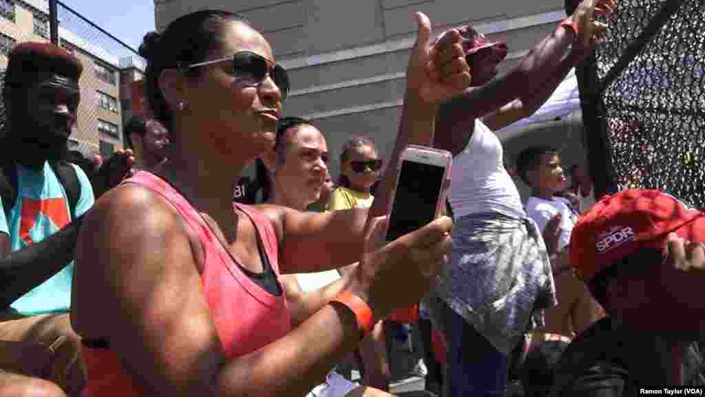 Marilyn Morales cheers on her son Ian from the stands at the Harlem RBI Field of Dreams, New York, Aug. 12, 2016.