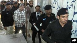 A US consulate employee identified by Pakistani authorities as Raymond Davis is escorted by police and officials in Lahore, Pakistan