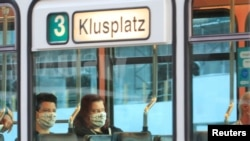 Passengers wear protective masks as they sit in a tram of public transport in Switzerland
