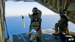 A photo taken on March 20, 2014, shows Royal Australian Air Force Loadmasters, Sergeant Adam Roberts (L) and Flight Sergeant John Mancey (R), preparing to launch a Self Locating Data Marker Buoy from a C-130J Hercules aircraft.