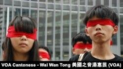 學民思潮發言人周庭(左)及召集人黃之鋒以紅布蒙眼,代表中國的紅色政權蒙蔽學生