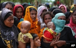 Rohingya women carry children and wait for food handouts at Thangkhali refugee camp in Cox's Bazar, Bangladesh, Oct. 5, 2017.