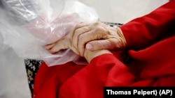 """Gregg MacDonald holds hands with his 84-year-old mother, Chloe MacDonald, at a """"hug tent"""" set up outside the Juniper Village assisted living center in Louisville, Colorado, on Wednesday, Feb. 3, 2021. (AP Photo/Thomas Peipert)"""