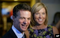 FILE - Republican David Trott, candidate for Michigan's 11th congressional district at the time, stands next to his wife, Kappy, during an interview at his election night party in Troy, Michigan, Aug. 5, 2014. In a statement Monday, Trott said he will not run for reelection.