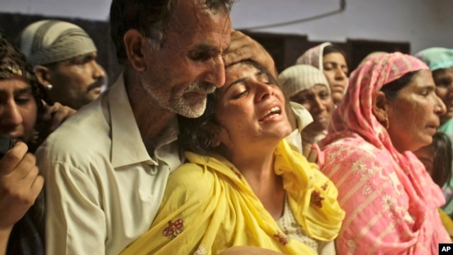 A Pakistani man comforts his relative mourning the death of a family member killed in gas cylinder explosion on a minibus, in Gujrat, Pakistan, May 25, 2013.