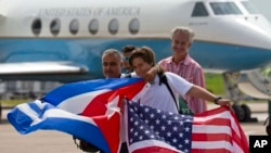 31일 제트블루 387편으로 미국 플로리다주를 떠나 쿠바 산타 클라라에 내린 승객들이 미국과 쿠바 국기를 들고 미 정부 항공기 앞에서 기념사진을 찍고있다.