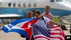 Para penumpang pesawat Jet Blue nomor penerbangan 387 mengibarkan bendera Kuba dan AS usai mendarat di Santa Clara, Kuba, Rabu (31/8).