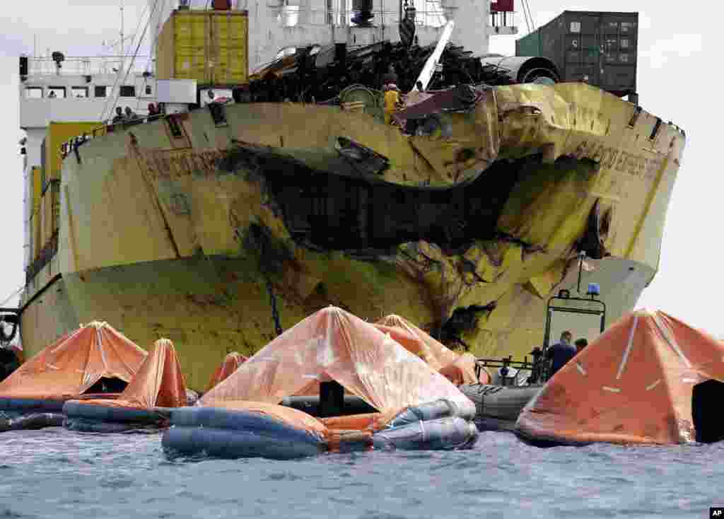 A cluster of life rafts floats near the cargo ship Sulpicio Express Siete a day after it collided with a passenger ferry off the waters of Talisay city, Cebu province in central Philippines. Divers combed through a sunken ferry to retrieve the bodies of more than 200 people still missing from an overnight collision.