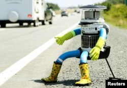 The anthropomorphic robot named hitchBOT sits on the shoulder of Highway 102 to begin its 6000 kilometer cross country journey outside of Halifax, Nova Scotia, July 27, 2014.