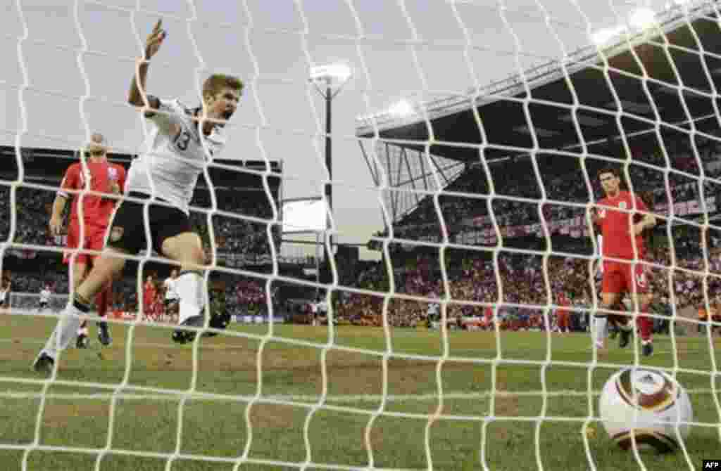 Томас Мюллер (Германия), второй слева, празднует его гол в матче между Германией и Англией на стадионе «Free State Stadium» в Блумфонтейн, Южная Африка. Воскресенье, 27 июня 2010г. (Фото АП / Гере Брелоер)