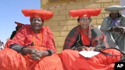 Herero women attend a gathering in Okokarara, Namibia, Aug. 14, 2004 where Germany's Development Aid Minister, Heidemarie Wieczorek-Zeul, unseen, offered Germany's first apology for a colonial-era crackdown that killed 65,000 ethnic Hereros between 1904 and 1908.