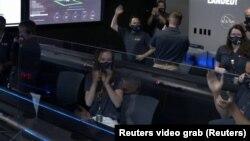 Les membres de l'équipe applaudissent l'atterrissage du rover Perseverance sur Mars.