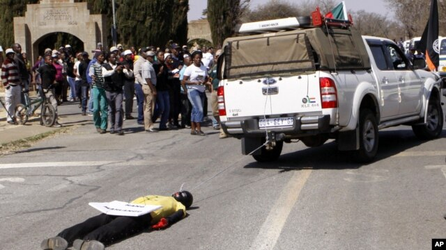 An effigy of the killer of right wing leader Eugene TerreBlanche is dragged behind a vehicle past protesters outside the court in Ventersdorp, South Africa, August 22, 2012.