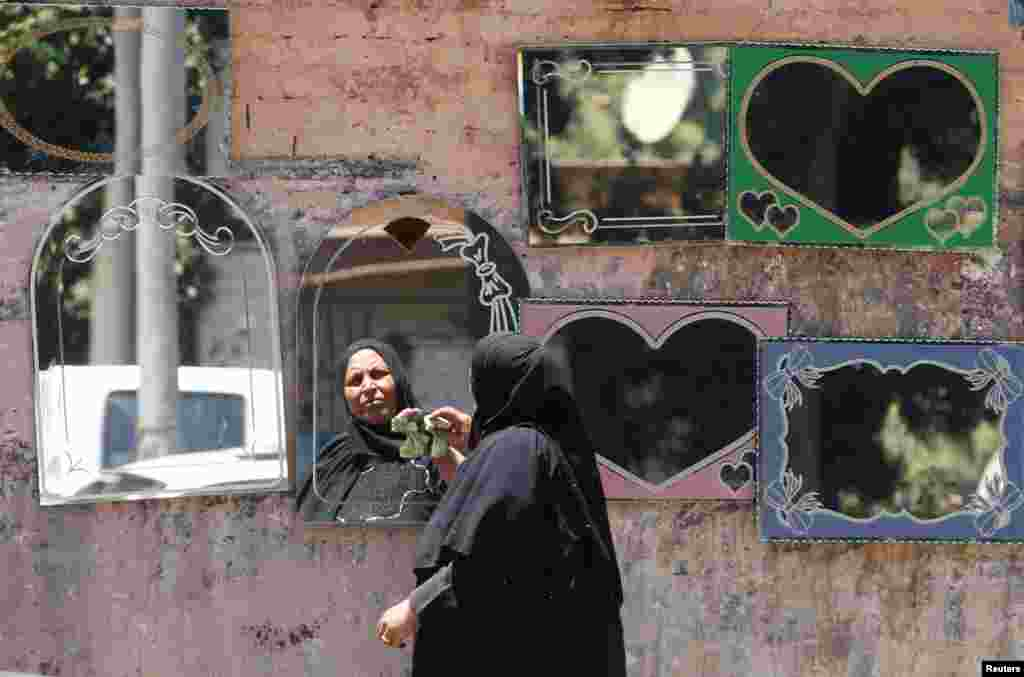 An Egyptian woman cleans her mirrors for sale on the street near the Nile island of al-Warraq, one day after security forces clashed with residents while attempting to demolish illegal buildings, in the south of Cairo, Egypt.