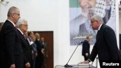 Menlu Palestina Riyad al-Maliki (kanan) mengambil sumpah jabatan di hadapan Presiden Palestina Mahmoud Abbas dalam pelantikan pemerintahan persatuan di Ramallah (2/6).