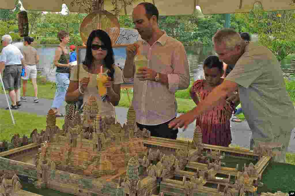 Participants carefully studying a replica of Angkor Wat, Cambodia's famed medieval temple. The 5,000-dollar replica was commissioned from Cambodia.
