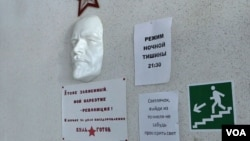 """A face mask of Russian communist revolutionary Vladimir Lenin is seen mounted on a wall at the Vershina-Navigator Foundation's rehabilitation center. The sign beneath reads """"I'm also addicted. Revolution is my narcotic!"""""""