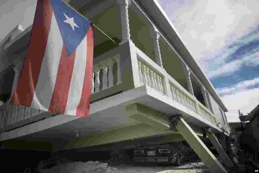 Una bandera puertorriqueña cuelga del porche de una casa que se derrumbó encima de automóviles estacionados después de un terremoto en Guánica, Puerto Rico, el lunes 6 de enero de 2020.