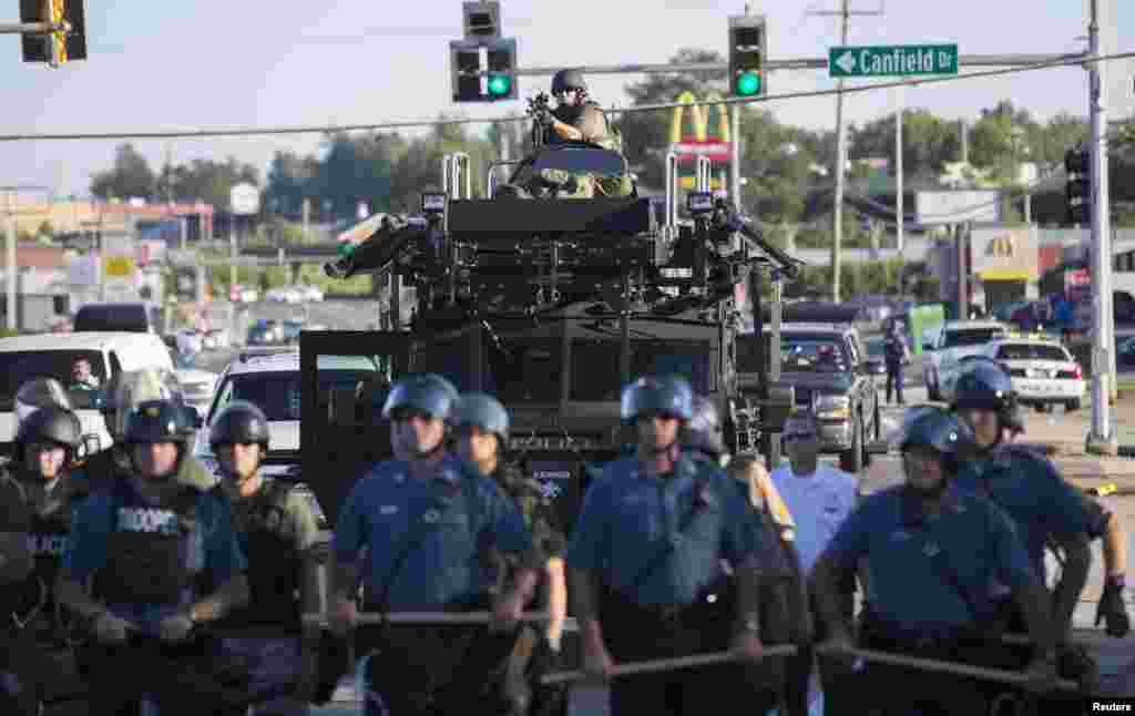 Riot police stand guard as demonstrators protest the shooting death of teenager Michael Brown, in Ferguson, Missouri Aug. 13, 2014.
