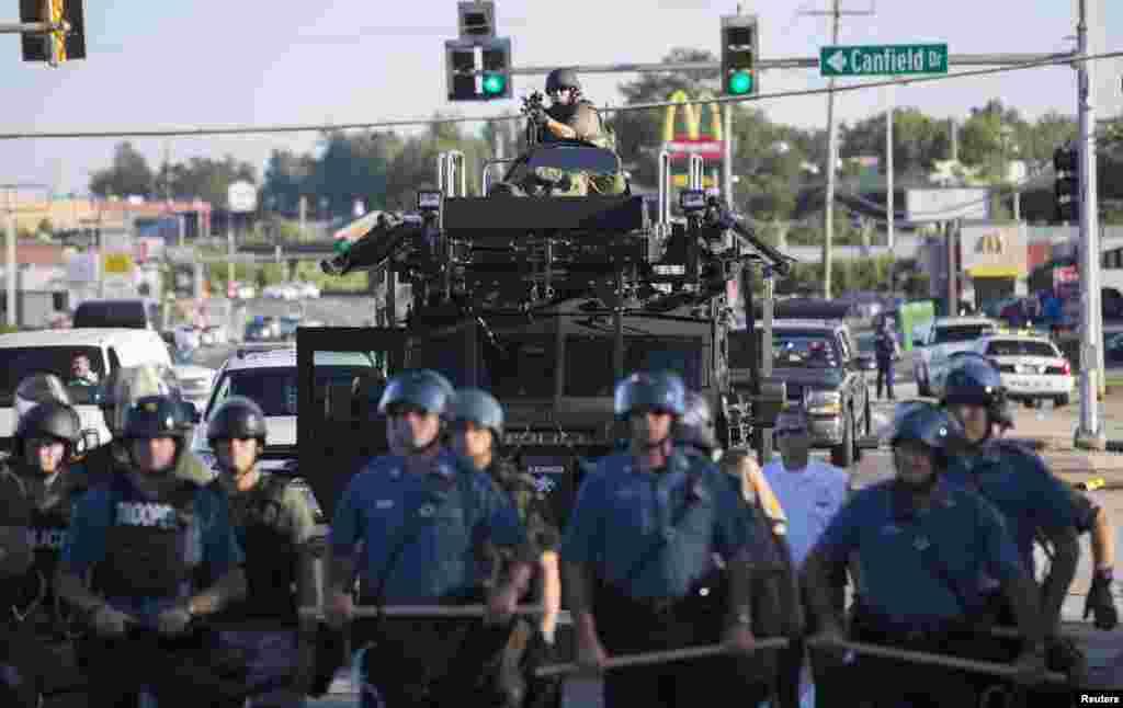 Polícia de choque americana de guarda, enquanto os manifestantes protestam contra a morte a tiro do jovem de 18 anos, Michael Brown, em Ferguson, Missouri Ago. 13, 2014.