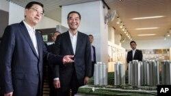 Ông Trương Đức Giang, chủ tịch Ủy ban Thường vụ Đại hội Đại biểu Nhân dân Toàn quốc của Trung Quốc (trái) và Trưởng đặc khu hành chính Hong Kong Lương Chấn Anh (phải) nhìn vào mô hình các khu nhà ở công cộng mới được xây dựng dự kiến đưa vào sử dụng cuối năm nay tại Hong Kong, ngày 19 tháng 5 năm 2016.