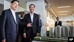 Zhang Dejiang (l) chairman of China's National People's Congress, and Hong Kong Chief Executive Leung Chun-ying (r) look at a model of newly built public housing blocks due to open later this year in Hong Kong on May 19, 2016.