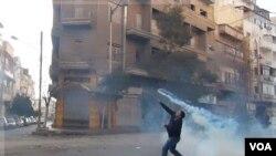 Seorang pengunjuk rasa melemparkan kembali gas air mata ke arah petugas keamanan di pusat kota Homs, Suriah (Foto: dok).