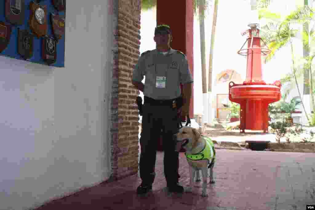 Un oficial de policía y su perro en el centro de bienvenida en Cartagena. (Iscar Blanco, VOA)