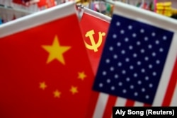 China, FILE PHOTO: The flags of China, U.S. and the Chinese Communist Party are displayed in a flag stall at the Yiwu Wholesale Market in Yiwu, Zhejiang province