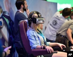 A woman wears a virtual reality display at a computer and video game event in Cologne, Germany, Aug. 5, 2015.