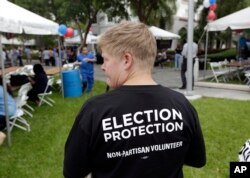 FILE - Lisa Hubbard, a volunteer with the non-partisan Election Protection Coalition, attends an early voting celebration outside of Jackson Memorial Hospital, on the first day of early voting in Miami-Dade County for the general election in Miami, Oct. 24, 2016. OAS and OSCE observers will participate in the U.S. election.