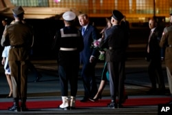 President Donald Trump and first lady Melania Trump pass an honor guard as they walk toward their vehicle after arriving at Chopin Airport, in Warsaw, Poland, July 5, 2017.