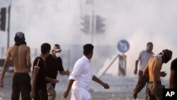 Riot police fire tear gas Friday, Sept. 16, 2011, in Sitra, Bahrain.