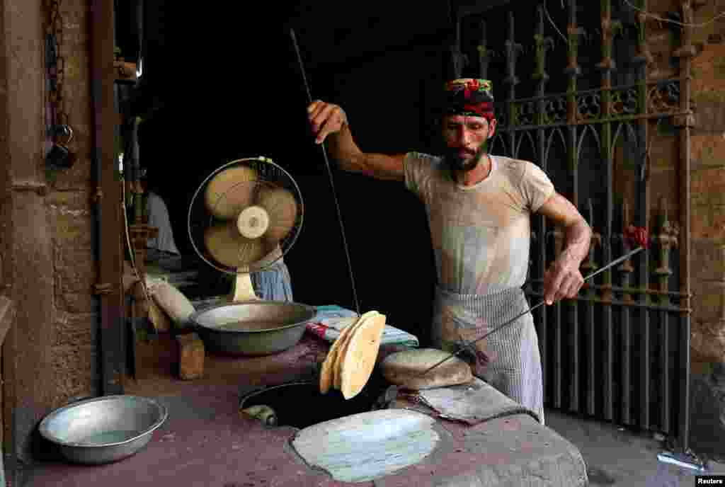 A worker collects bread from the oven while preparing and selling them at the entrance of a building in Karachi, Pakistan.
