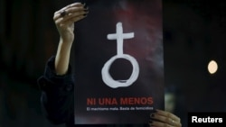 FILE - A woman holds up a poster with female symbol during a demonstration demanding policies to prevent femicides in Buenos Aires, Argentina, June 3, 2015.