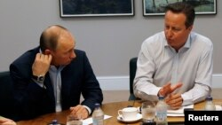 Russia's President Vladimir Putin (L) talks with Britain's PM David Cameron during a working session at the Lough Erne golf resort where the G8 summit is taking place in Enniskillen, Northern Ireland, June 18, 2013.