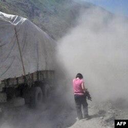 美国之音记者何宗安被汽车卷起的漫天尘土包围