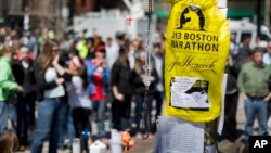 Visitors pause at a makeshift memorial in Copley Square for victims of the Boston Marathon bombings, Apr. 27, 2013, in Boston, Mass.