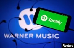 "Layanan streaming musik ""Spotify"" dan logo label ""Warner Music"". (Foto: ilustrasi)."
