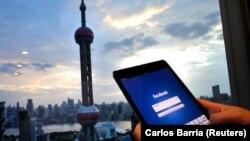 Seorang pria membuka laman Facebook di iPadnya di distrik keuangan Pudong di Shanghai, China, 25 September 2013. (Foto: Carlos Barria/Reuters)