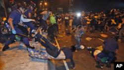 Polisi Hong Kong berusaha membersihkan para demonstran yang memblokade jalanan di Hong Kong (1/12).
