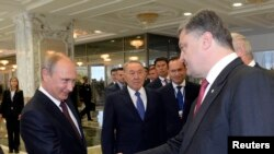 FILE - Russian President Vladimir Putin (L) shakes hands with his Ukrainian counterpart Petro Poroshenko at the start of talks in Minsk, Belarus, Aug. 26, 2014.