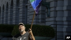 Gay marriage supporter Bob Sodervick holds up a flag outside of the 9th Circuit Court of Appeals in San Francisco, June 5, 2012.