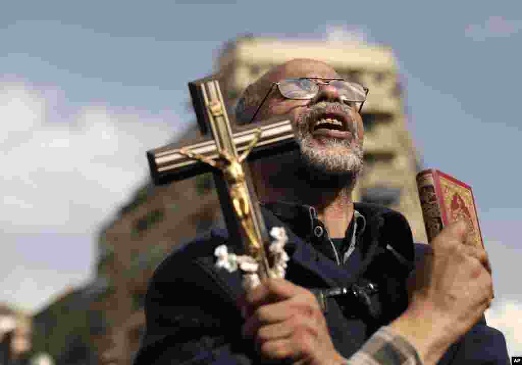 An Egyptian protester chants slogans and holds a cross and a Quran in Tahrir Square, Cairo, Egypt, November 23, 2012.