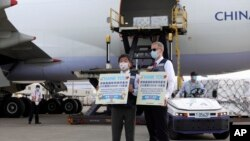 In this photo released by the Taiwan Centers for Disease Control, Taiwan's Health Minister Chen Shih-chung, left, and Brent Christensen, the top U.S. official in Taiwan, hold up thank you cards as they welcome a China Airlines cargo plane carrying COVID-1