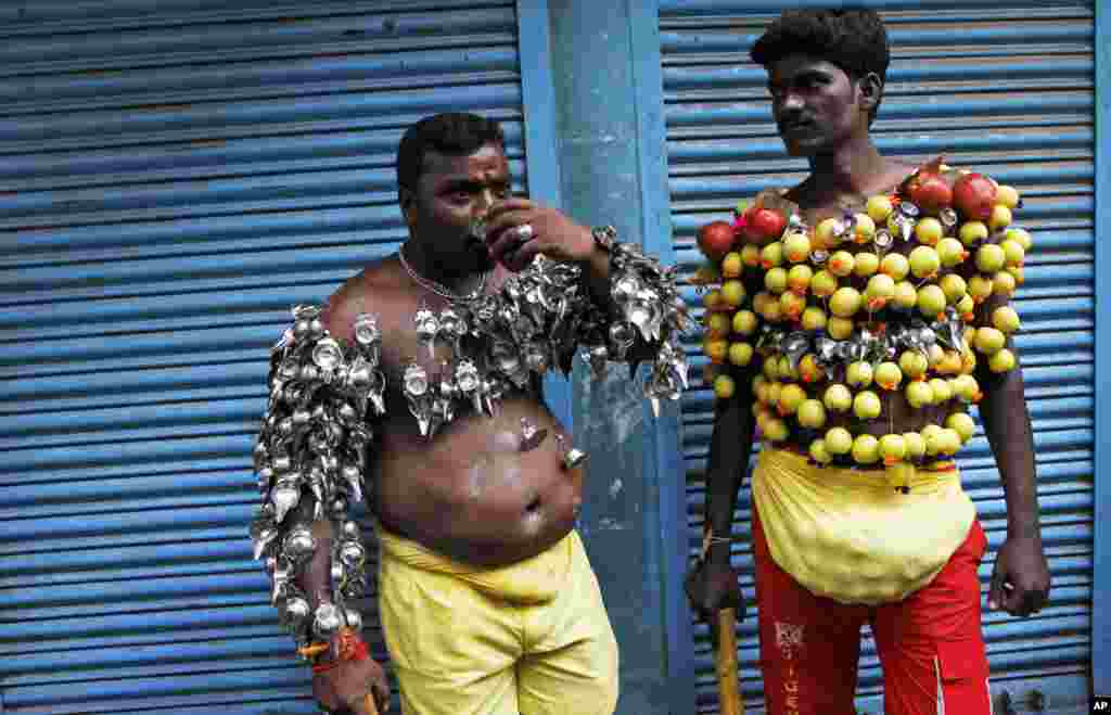 Hindu devotees, their bodies pierced with lemon and paladai, or bowl with a spout mainly used to feed milk to infants, wait to participate in a procession to mark Shivratri, or the night of Shiva, in Chennai, India.
