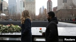 FILE - Attendees wait to leave roses during a commemoration ceremony of the 25th anniversary of the 1993 World Trade Center bombing at the north reflecting pool of the National September 11 Memorial & Museum at the World Trade Center site in the Manhattan borough of New York, Feb. 26, 2018.